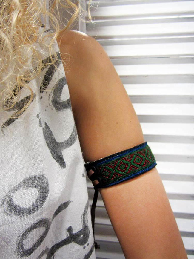 Leather bracelet with a green woven ribbon and Aztec pattern