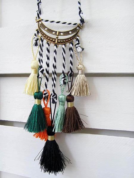Pendant with an adjustable height cord and several rayon tassels with a bronze metal moon-shaped trim