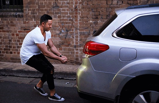 Man in a white t-shirt pulling a silver sedan with his Infinity magnetic cable. First universal magnetic charging cable to support 100W PD Charge, QC3.0/4.0 & Data Transfer for Apple, Micro USB, USB C & USB-C Laptops including Macbook Pro.