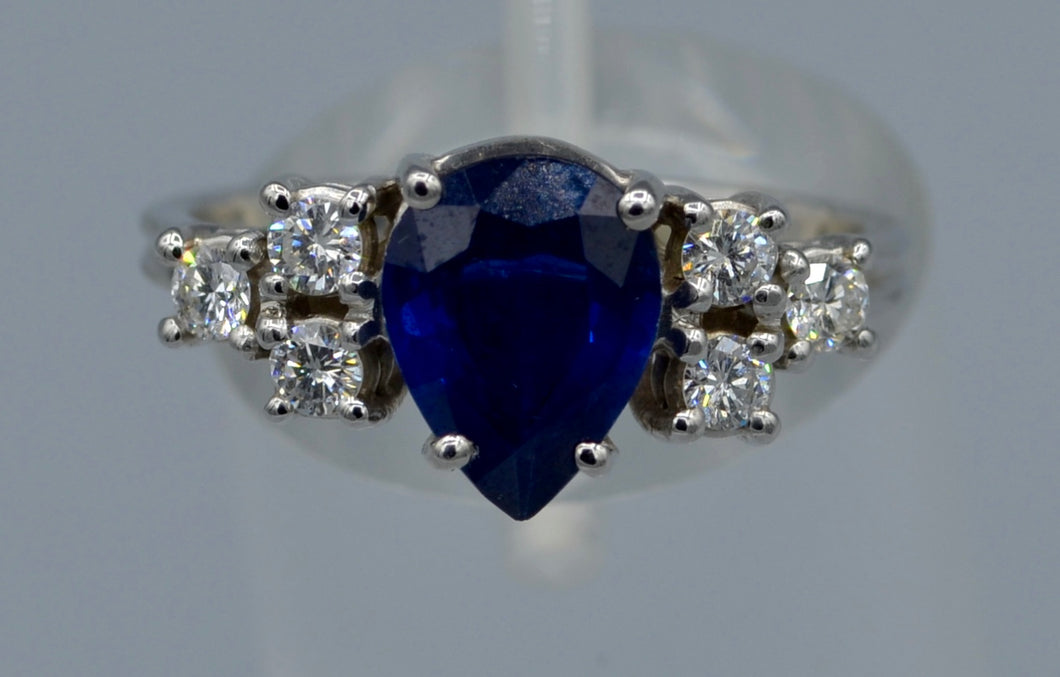 14K white gold ring with one center Sapphire and six side diamonds