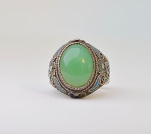 Jade cab set in silver ring with ornate designs