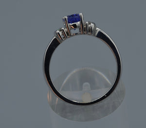 14K white gold ring with one center oval Tanzanite and four side diamonds