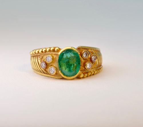 18 Karat yellow gold ring with one center Emerald  and six side diamonds.