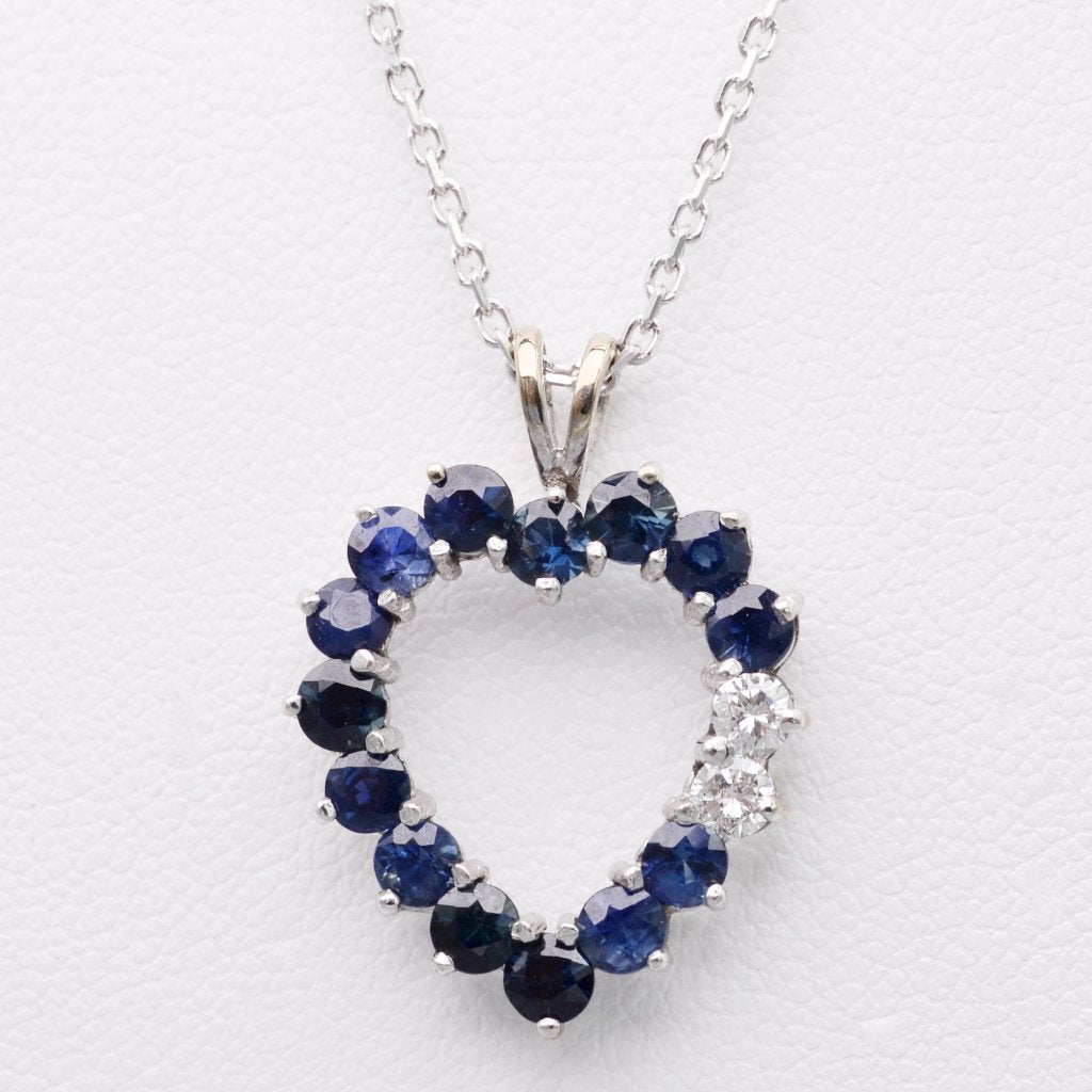 14K white gold heart-shaped pendant with fourteen Sapphires and two Diamonds