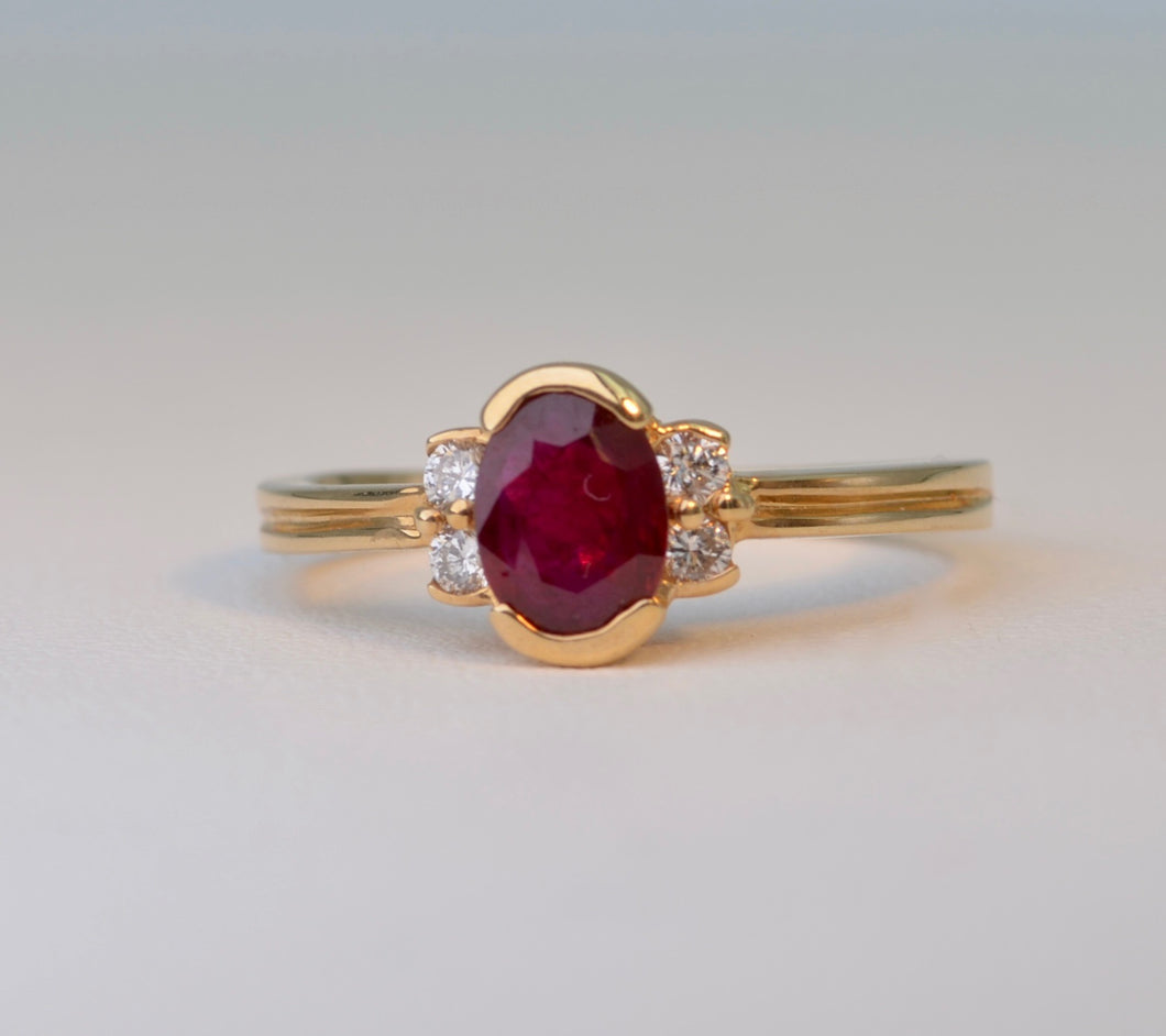 14K yellow gold ring with one center oval Ruby and four side Diamonds