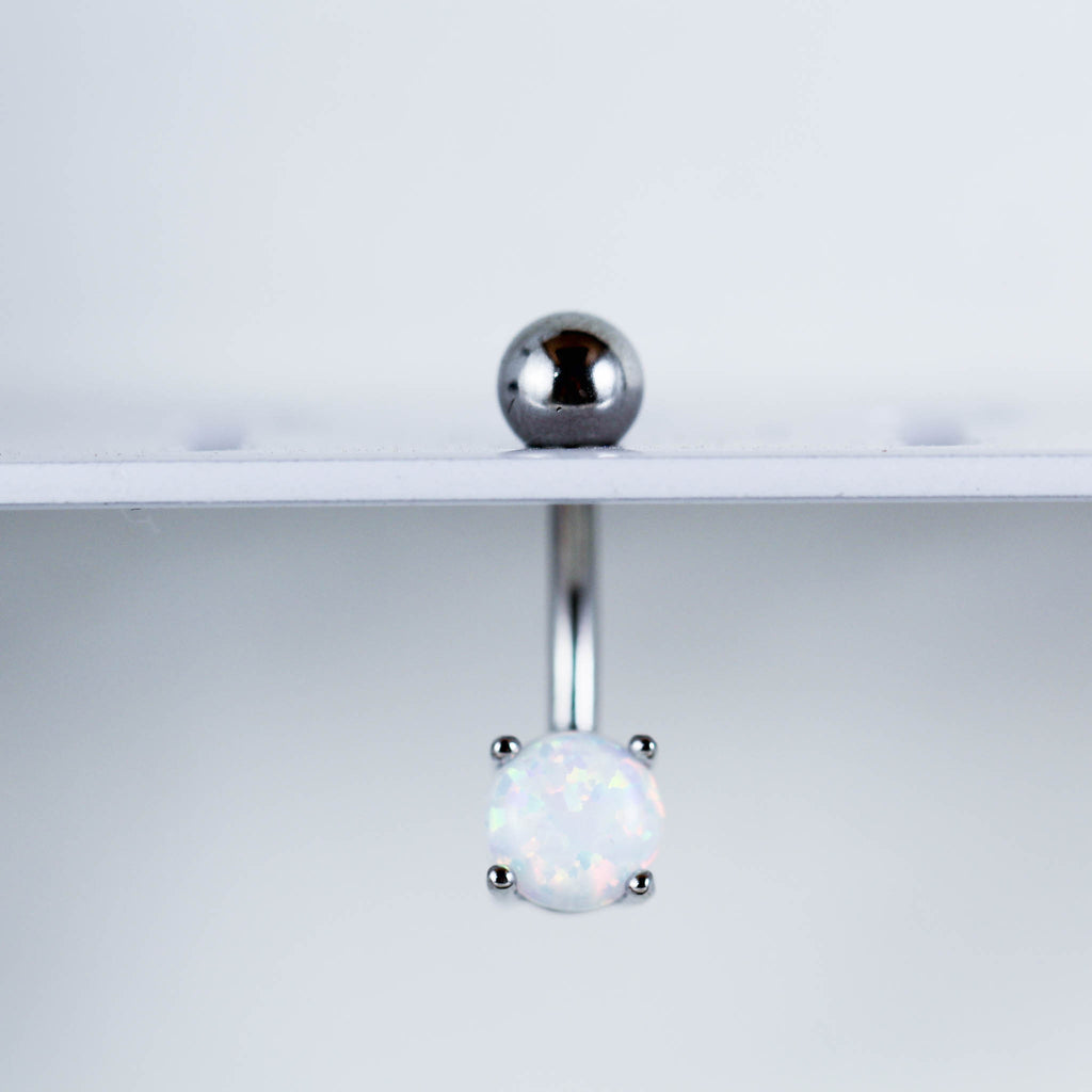 Silver and White Opal Belly Ring Hanging on Piercing Display