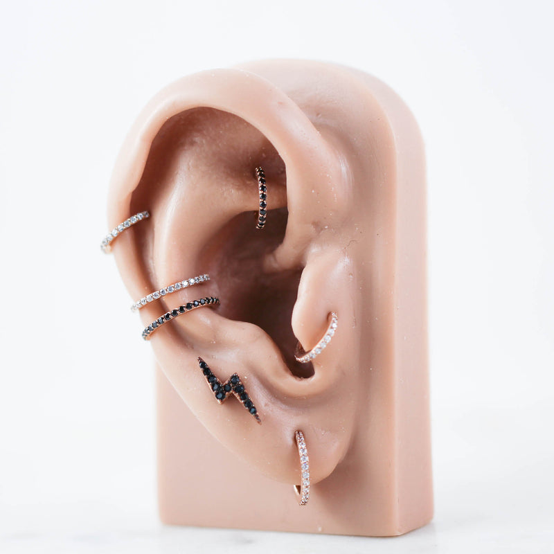 Rose Gold and Black Piercing Jewelry on Ear Model. Cute Ear Piercings with Crystal Paved Hinged Seam Rings.