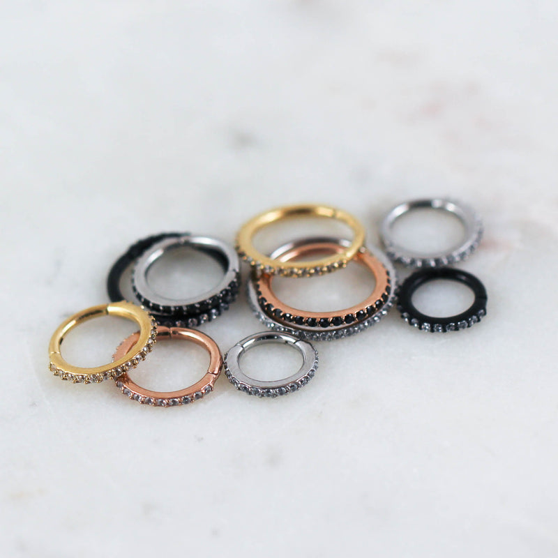 Crystal Paved Hinged Seam Rings seen in Gold with Clear Crystals, Rose Gold with Black Crystals, Silver with Clear Crystals, Silver with Black Crystals, or Black with Clear Crystals