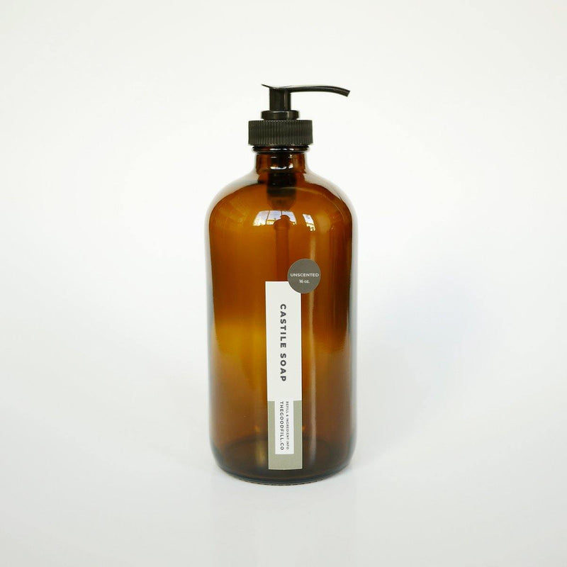 Product image of a 16oz glass amber bottle with a black pump top for zero waste unscented castile soap refills.