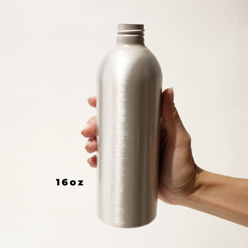 A hand holding a 16oz aluminum bottle for The Good Fill zero waste refills.