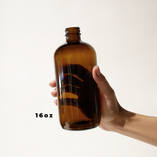 A hand holding a 16oz glass amber bottle for The Good Fill zero waste refills.