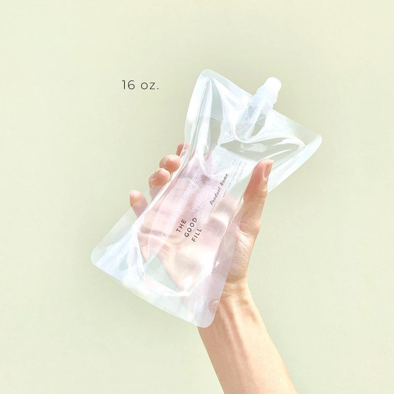 hand holding a zero waste 16oz. clear bulk re-fill pouch for package free lavender geranium conditioner refills