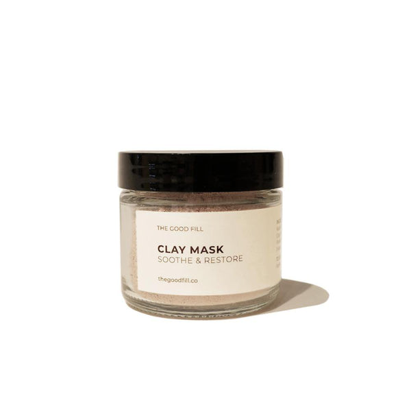 Product image of a 2oz. re-usable clear Good Fill glass jar filled with a light pink clay mask powder. The lid is a black twist-on lid.