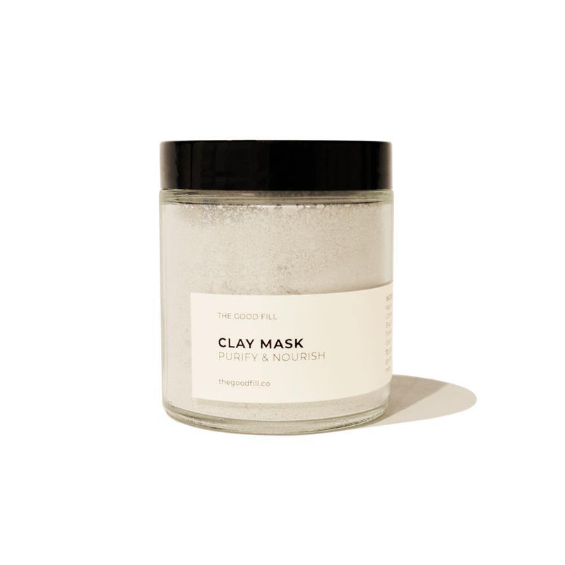 Product image of a 4oz. re-usable clear Good Fill glass jar filled with a light grey clay mask powder. The lid is a black twist-on lid.