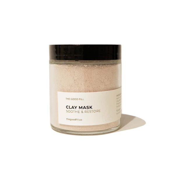 Product image of a 4oz. re-usable clear Good Fill glass jar filled with a light pink clay mask powder. The lid is a black twist-on lid.
