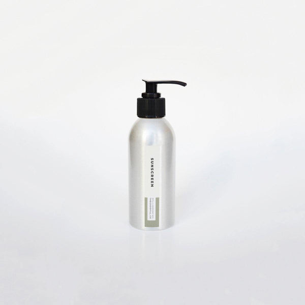 Product image of a 4oz aluminum bottle with a black pump top for zero waste green tea sunscreen refills.