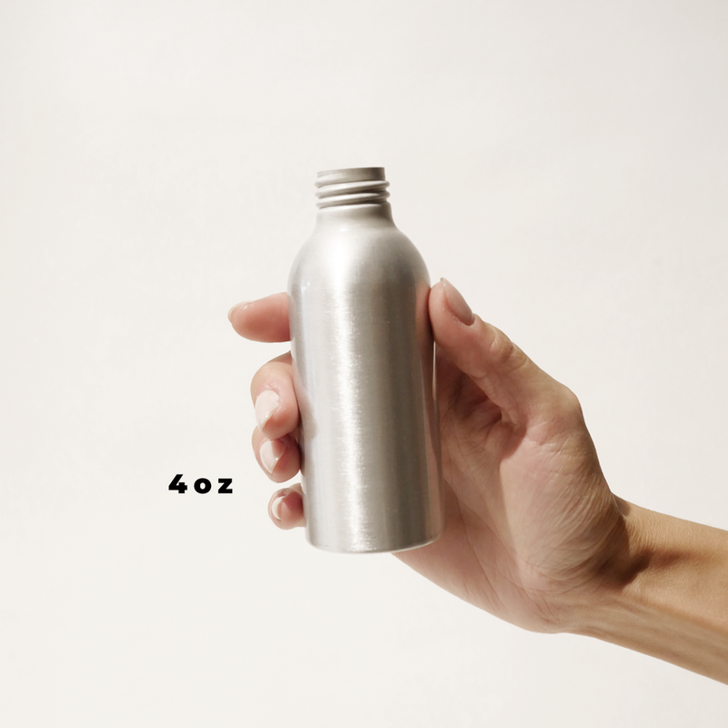 A hand holding a 4oz aluminum bottle for The Good Fill zero waste refills.