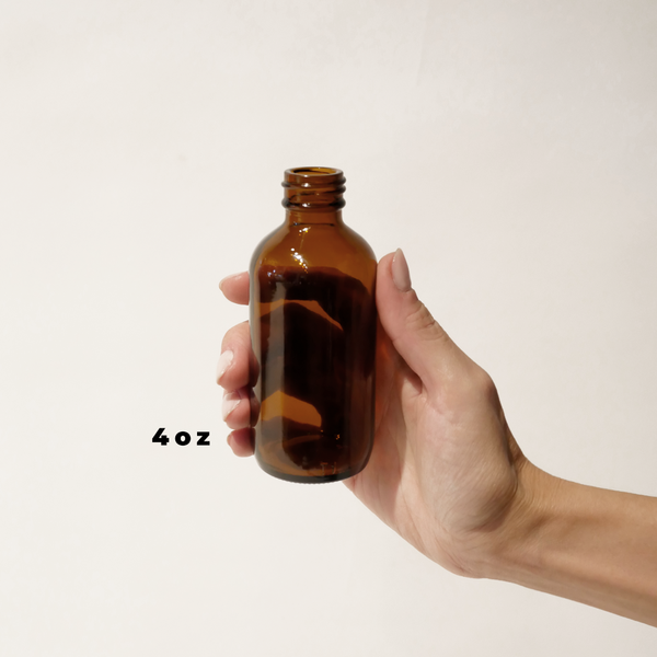 A hand holding a 4oz glass amber bottle for The Good Fill zero waste refills.