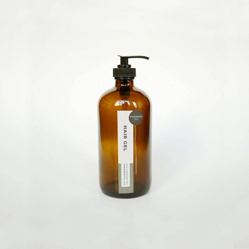 Product image of an 8oz glass amber bottle with a black pump top for zero waste unscented hair gel refills.