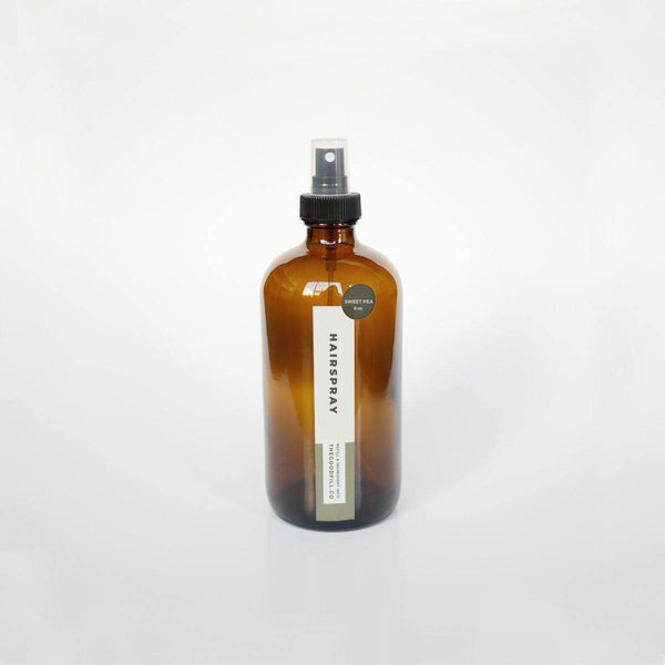 product image of 8oz. amber glass bottle with black spray top, rectangle product label, and round scent sticker for zero waste hairspray refills