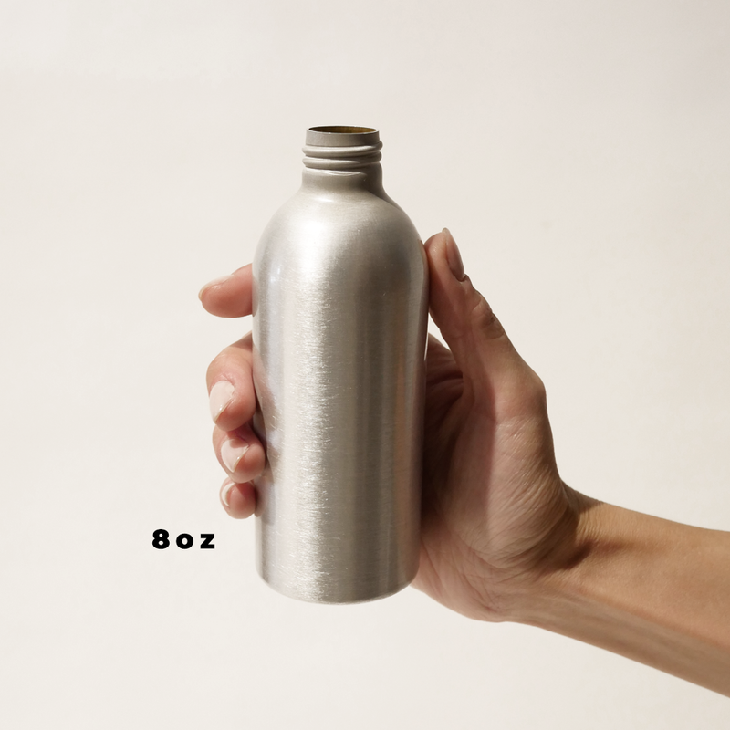 A hand holding an 8oz aluminum bottle for The Good Fill zero waste refills.