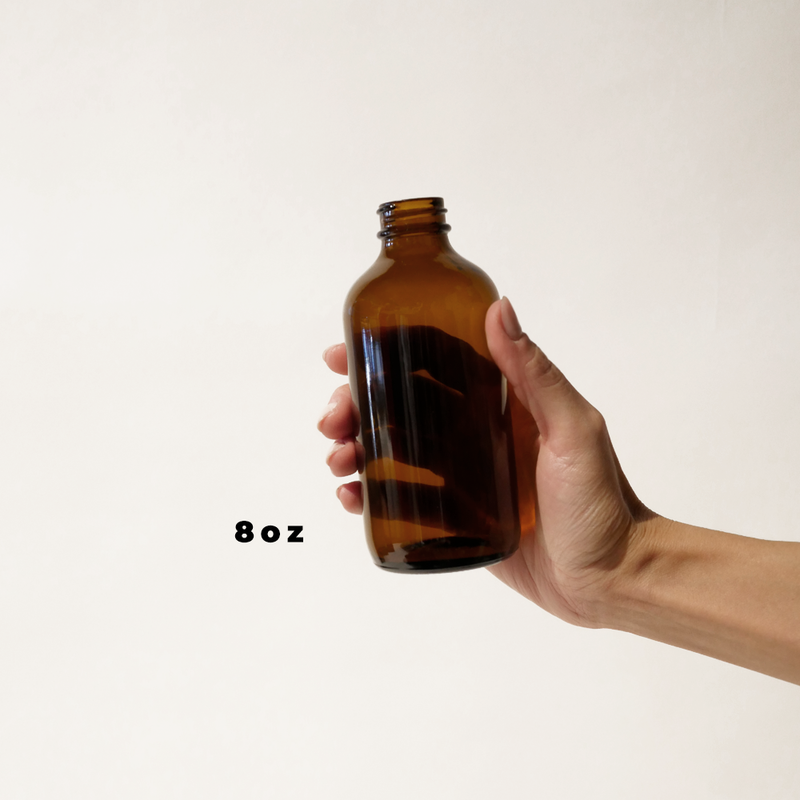 A hand holding an 8oz glass amber bottle for The Good Fill zero waste refills.