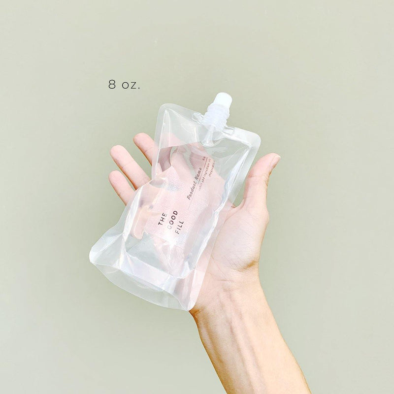 hand holding a zero waste 8oz. clear bulk re-fill pouch for package free face and body lotion