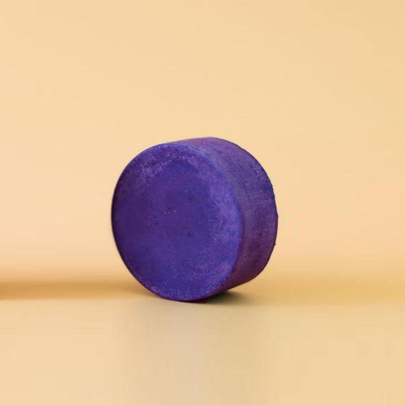Product image of a zero waste conditioner bar. The bar is a round deep purple toner conditioner bar.