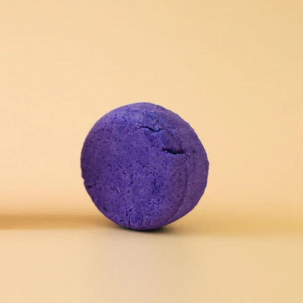 Product image of a zero waste shampoo bar. The bar is a round deep purple toner shampoo bar.