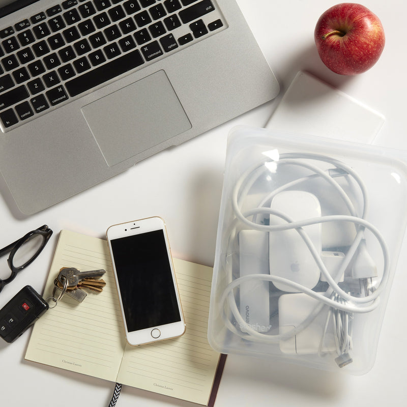 lifestyle image of a clear gallon sized stasher bag sitting on an office desk. The stasher bag is holding a computer charger along with other electronic chords.