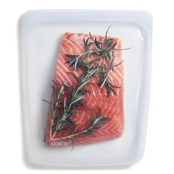 image of a reusable, zero waste clear gallon sized stasher bag containing a cut of uncooked salmon with rosemary.