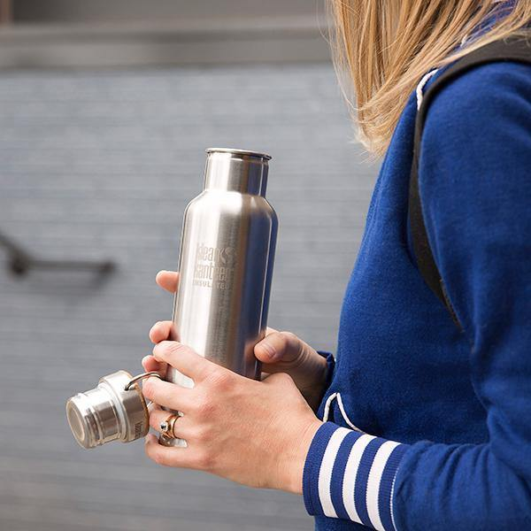 Lifestyle image of a woman holding a stainless steel Klean Kanteen bottle with the lid off.