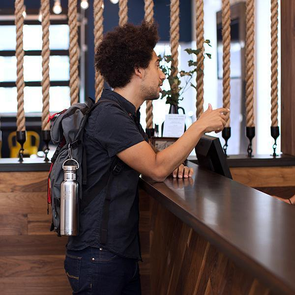 Lifestyle image of a young man standing at a hotel counter with a stainless steel Klean Kanteen bottle hanging from the side of his backpack. The Klean Kanteen is attached by a carabiner.
