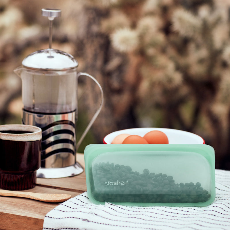 lifestyle image of a green snack sized stasher bag holding coffee beans and sitting on an outdoor picnic table. There is a coffee cup and french press sitting on the table next to the stasher bag.