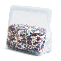 product image of a reusable, zero waste clear stand-up stasher bag. The bag is holding an assortment of uncooked dry beans.