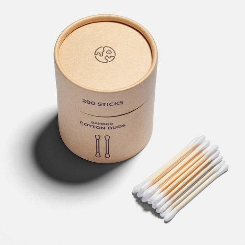 product image of the bamboo cotton buds brown kraft paper container with a lift-off kraft paper lid. There are white cotton ear buds sitting next to the container on a white background.