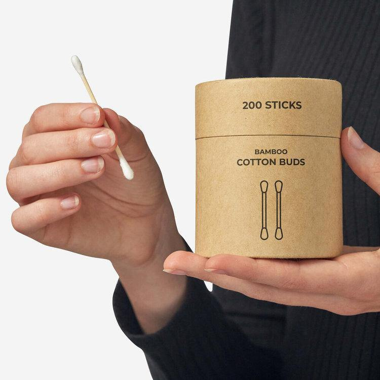 one hand is holding the round, brown kraft paper packaging and the other hand is holding one cotton ear bud