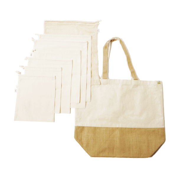 Flat lay of all the bags that are included in this zero waste bag bundle. The market bag is cream and brown jute color, and all the produce bags are a white cream color.