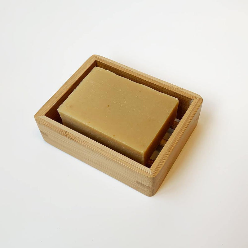 product shot of brown, rectangle bamboo soap dish holding a grapefruit lemon bar of soap