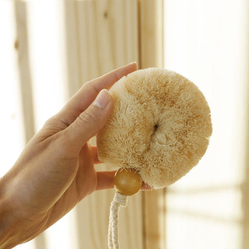 Hand holding the vegan body brush. The brush is a circular shape that will fit in the palm of the hand.