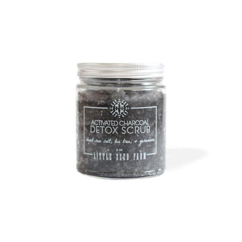 clear glass jar with white lid filled with dark grey activated charcoal scrub