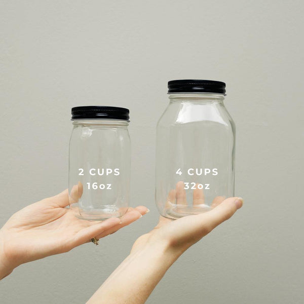 Hands holding two clear glass mason jars with  black aluminum twist off lids. One jar is 16oz and one jar is 32oz.