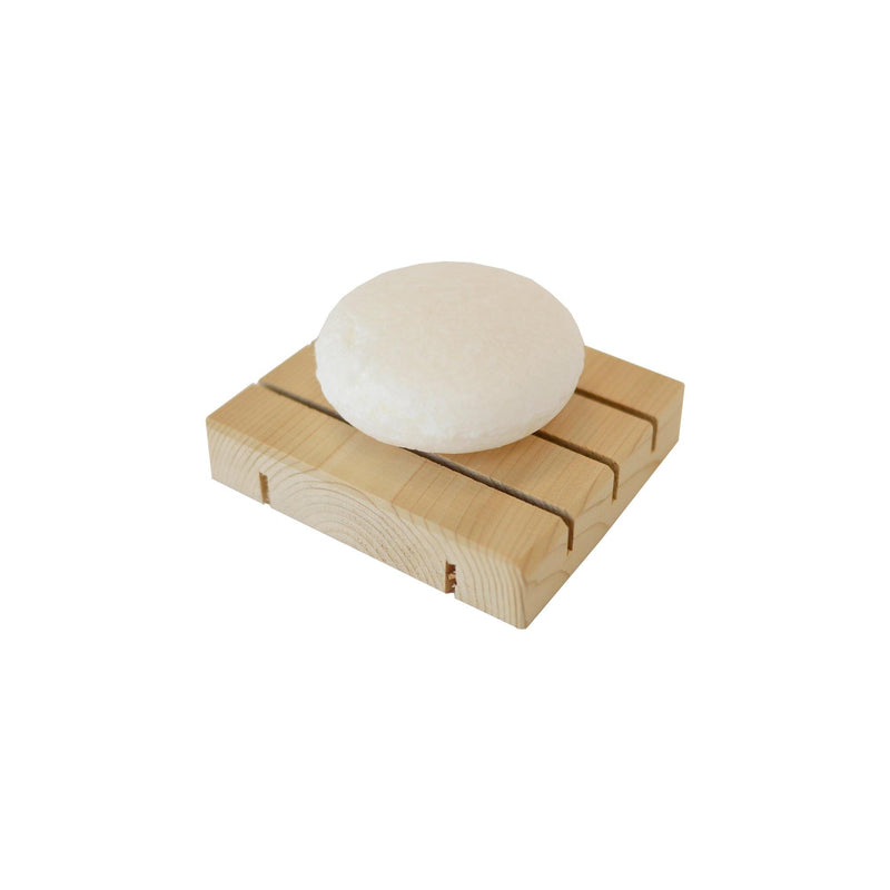 product image of a zero waste white, round dog shampoo bar sitting on a natural wooden soap dish.