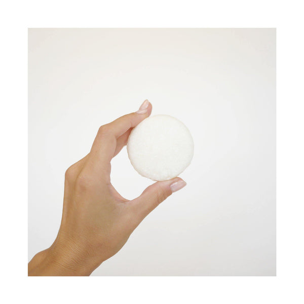 hand holding a white, round dog shampoo bar.