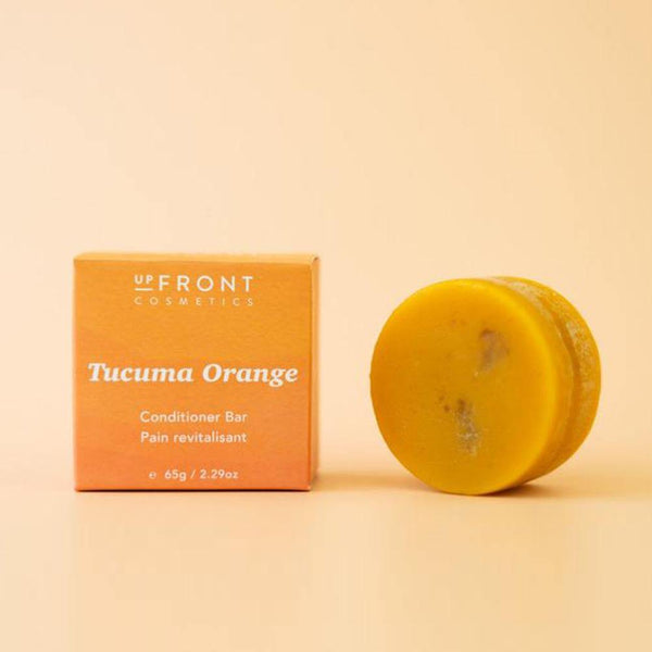 A round orange colored deep conditioner bar is sitting next to its square orange packaging kraft cardboard box.
