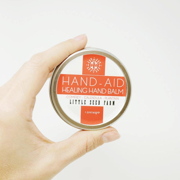 hand holding the round hand-aid tin to show size.