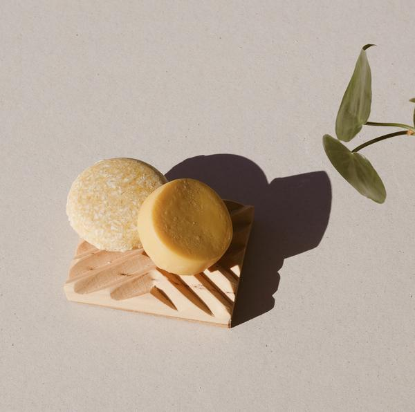 package free round yellow sweet citrus shampoo bar and round yellow sweet citrus conditioner bar sitting on a wooden soap dish