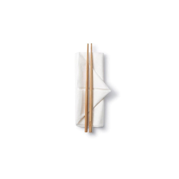 product image of a pair of reusable natural brown bamboo chopsticks sitting on a neatly folded white napkin.