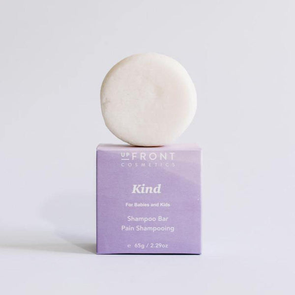 A white round kind shampoo bar is sitting on top of a purple kraft paper packaging box.