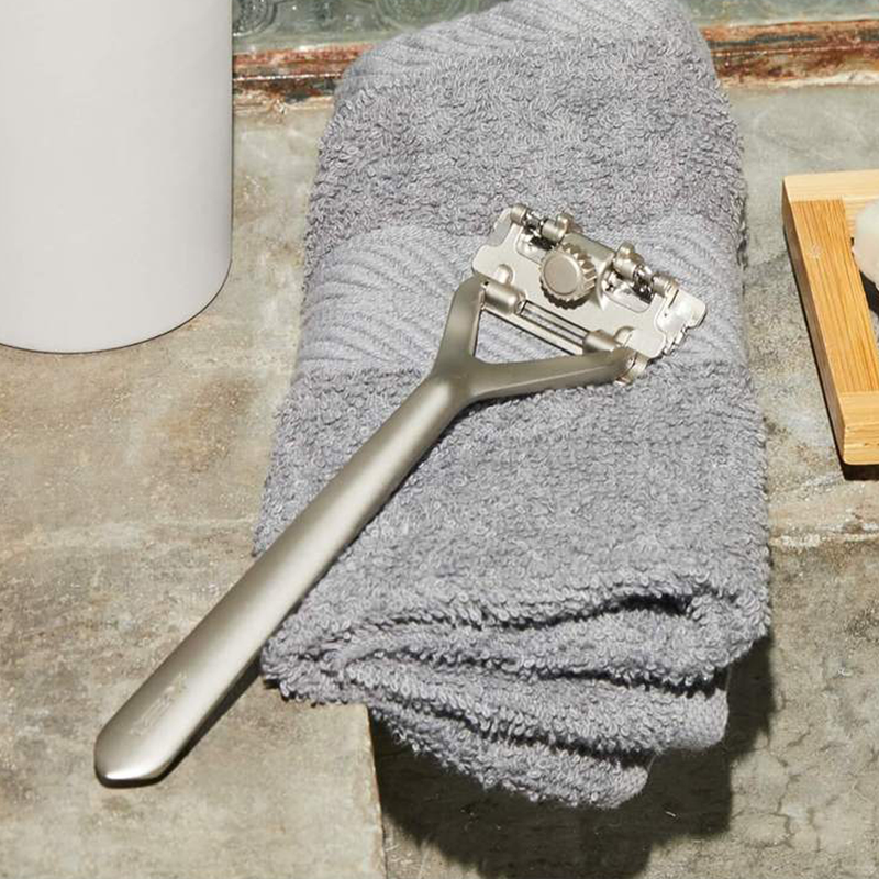 Silver Pivoting Triple Blade Razor by Leaf. The razor is sitting on a grey bath towel.
